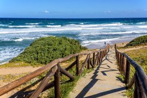 a picture of the wooden pathway that leads to the beach named Spiaggia di Lu Bagnu, near Castelsardo, north Sardinia, Italy.
