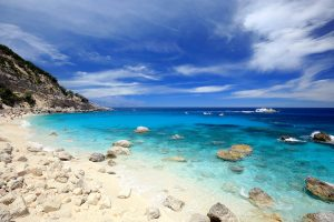 a picture of scattered rocks on the sandy beach of Cala dei Gabbiani, near Baunei, east Sardinia, Italy.