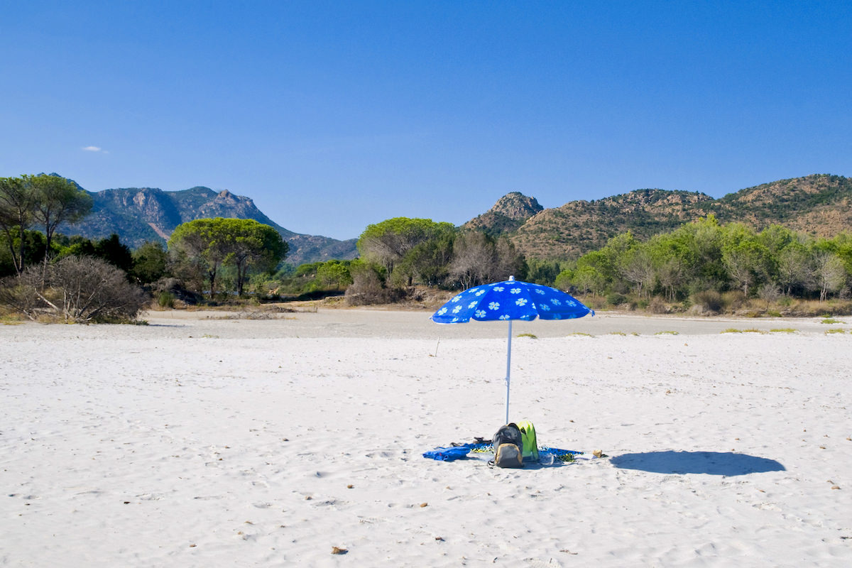 a picture of a blue umbrella on the beach named Spiaggia sa Curcurica, in Orosei, east Sardinia, Italy.
