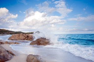 waves crashing on a few rocks at the beach of Cala Liberotto in east Sardinia Italy