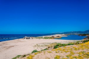 blues skies, a deep blue sea and a river at Spiaggia di San Pietro, in north Sardinia, Italy.